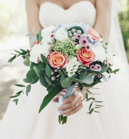 A Bride Holding Out Her Bouquet by Isla Bella's Waterfront Wedding Venues