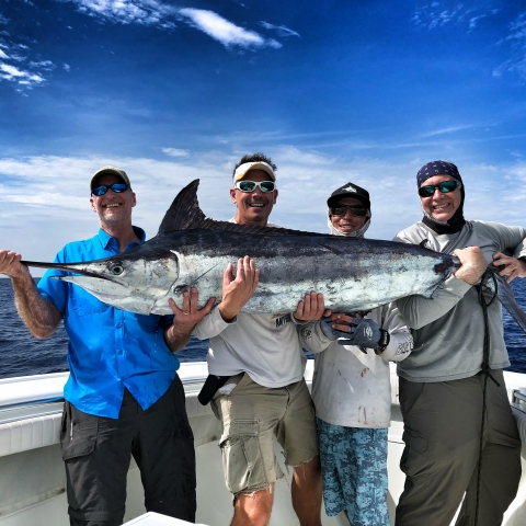 Group on boat with caught swordfish